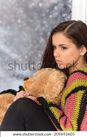 Portrait of pretty girl in sweater holding toy. Sad girl holding teddy bear