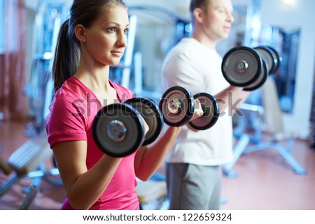 Portrait of pretty girl training in gym with young man near by
