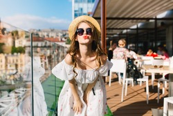 Portrait of pretty girl with long hair  in sunglasses standing  on the terrace in cafe . She wears a white dress with bare shoulders, red lipstick  and hat . She is making a kiss to the camera.