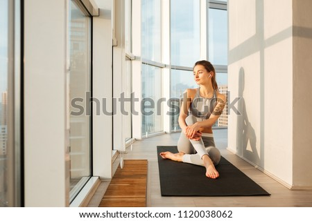 Portrait of pretty lady in sporty top and leggings sitting on yoga mat and thoughtfully looking in window at home isolated #1120038062