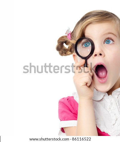 portrait of pretty little girl looking through  magnifying glass making faces mouth open isolated on white studio shot