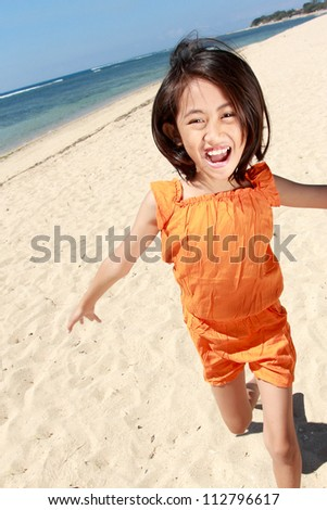 Portrait of pretty little girl running in the beach