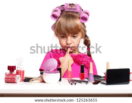 Portrait of pretty little girl seating at table with makeup accessories on white background