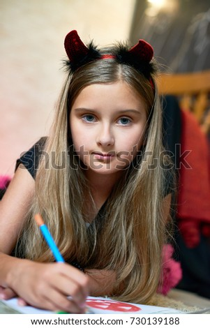 Portrait of pretty little girl wearing Halloween costume posing for photography while lying on carpet and drawing colorful picture, blurred background