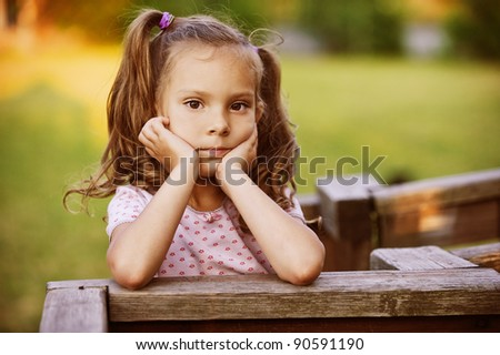 Portrait of pretty lovable little girl propping up her face at summer green park. - stock photo