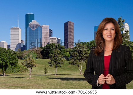 Portrait of pretty mature business woman wearing black jacket and red blouse.  City landscape in background.