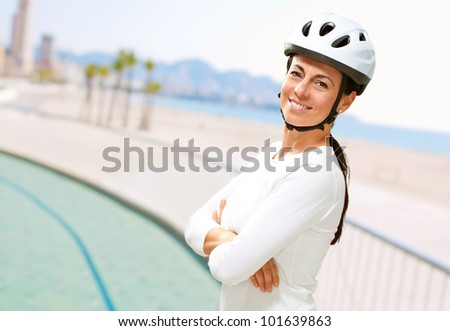portrait of pretty middle aged woman wearing a bicycle helmet near the beach