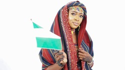Portrait of pretty Nigerian Hausa woman dressed in traditional attire and waving the national flag