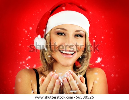 Portrait of pretty Santa girl laughing, isolated on red snowy winter holiday background