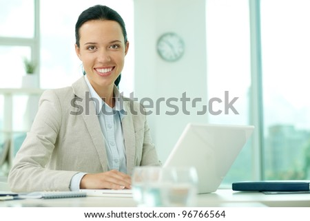 Portrait of pretty secretary looking at camera while working
