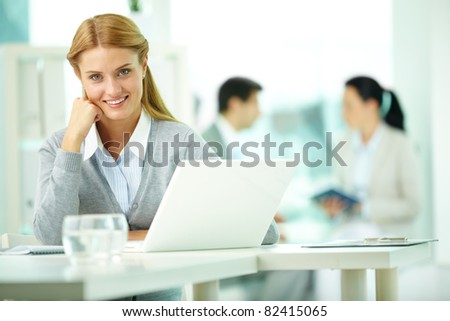 Portrait of pretty secretary working with her partners on background