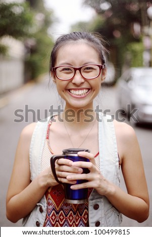 Portrait of Pretty Smiling Asian Girl Student With Glasses While Holding a Mug