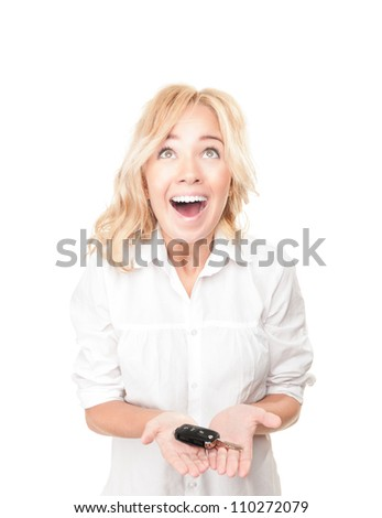 Portrait of pretty surprised young girl holding car key in her hands isolated on white background. Expression of shock, surprise and happiness. Woman got car as present or became winner.