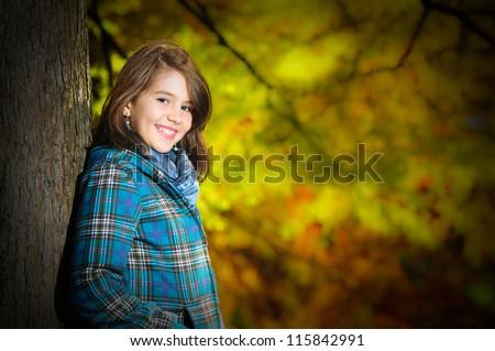 portrait of pretty teen girl in autumn park .Smiling happy girl portrait, autumn outdoor. - stock photo
