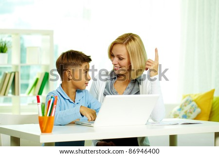 Portrait of pretty tutor and diligent pupil discussing ideas while working with laptop
