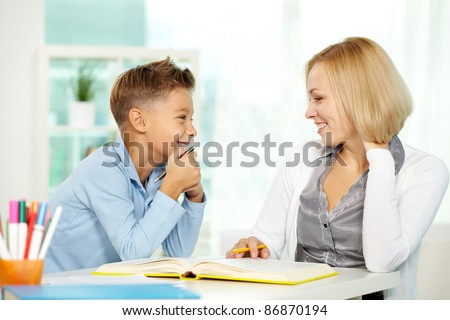 Portrait of pretty tutor and diligent pupil looking at each other while communicating