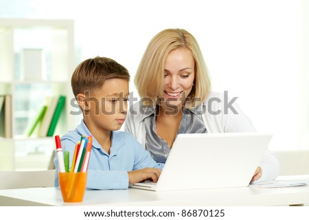 Portrait of pretty tutor and her pupil working with laptop