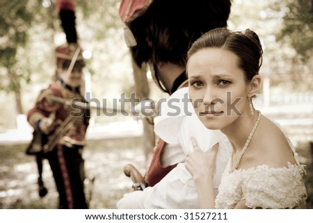 Portrait of pretty woman dressed in vintage dress and accessories. Dueling hussars on the background. Focus point on the girl.