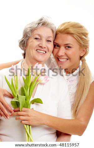 Portrait of pretty woman embracing her senior mother and holding tulips