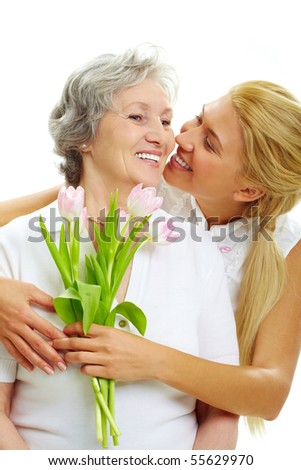 Portrait of pretty woman embracing her senior mother and holding tulips - stock photo