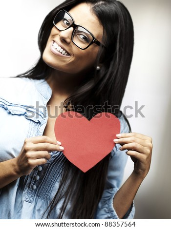 portrait of pretty woman holding a heart against a abstract background