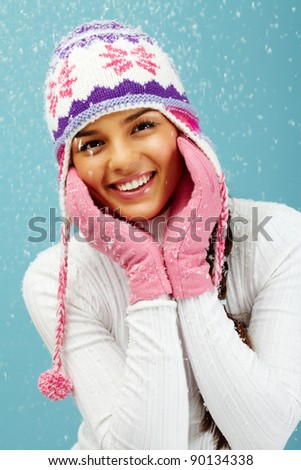Portrait of pretty woman in pink gloves and knitted winter cap looking at camera with smile