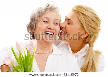 Portrait of pretty woman kissing and embracing her mother during holiday