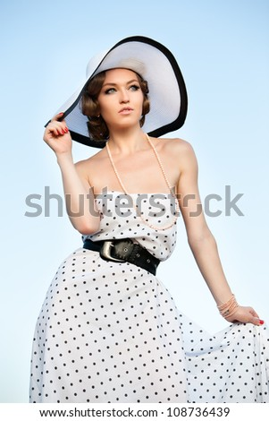 Portrait of pretty woman wearing white dress and straw hat in sunny warm weather day.  Walking at summer park.