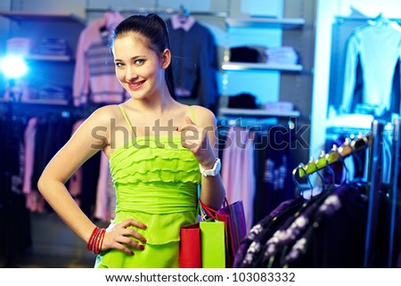 Portrait of pretty woman with paperbags looking at camera in clothing department