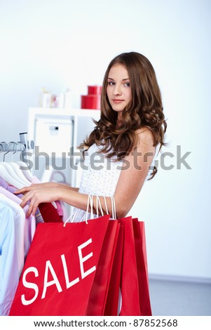 Portrait of pretty woman with red bags looking at camera in clothing department