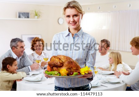 Portrait of pretty woman with roasted turkey on background of happy family