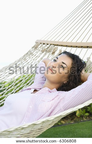 Portrait of pretty young adult Caucasian brunette female lying in hammock relaxing.