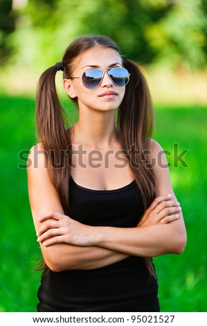 Portrait of pretty young brunette lady wearing black top and sunglasses at summer green park.
