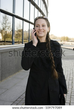 portrait of pretty young business woman talking on phone near building