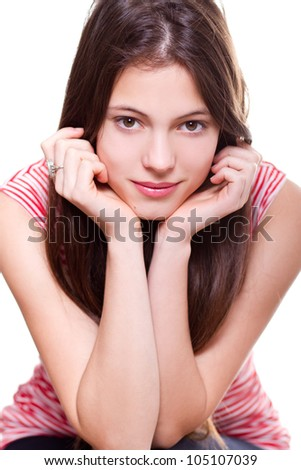 portrait of pretty young businesswoman sitting with hand on chin and smiling - isolated