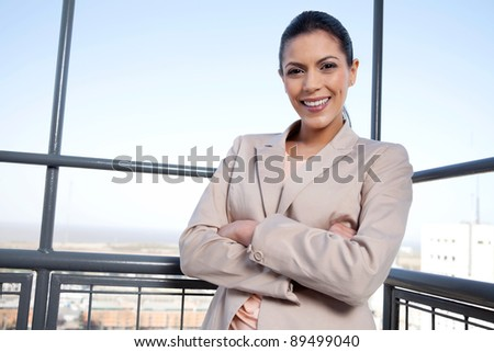Portrait of pretty young businesswoman smiling with arms crossed