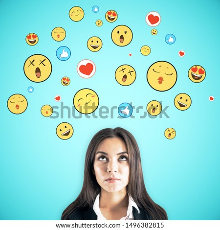 Portrait of pretty young businesswoman with emotive smileys on subtle blue background. Communication and emotion concept