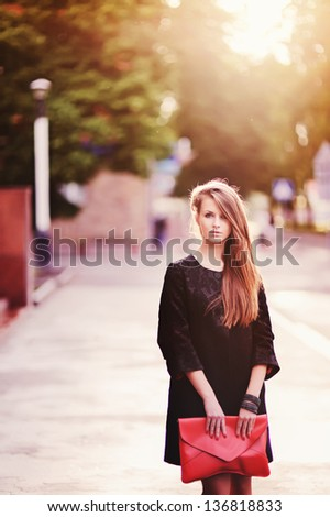 Portrait of pretty young female with a red bag in hands