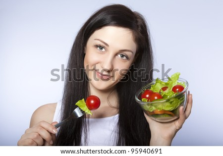 Portrait of pretty young girl eating vegetable salad