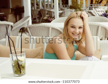 portrait of pretty young girl in cafe drinking coctail and smiling