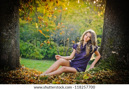 portrait of pretty young girl in the forest in autumn day.Portrait of pretty young female relaxing in forest in autumn day