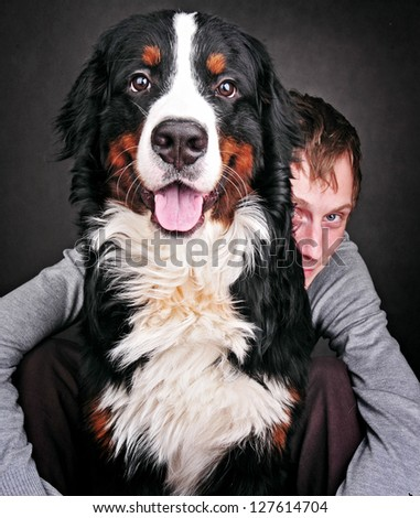 Portrait of Pretty young, happy, man with  beautiful Bernese mountain dog (Berner Sennenhund)