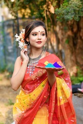Portrait of pretty young indian girl wearing traditional saree and jewellery, holding powder colours in plate on the festival of colours called Holi, a popular hindu festival celebrated across India.