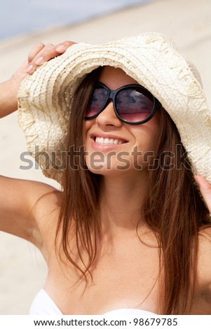 Portrait of pretty young lady in hat touching it and looking upwards through sunglasses