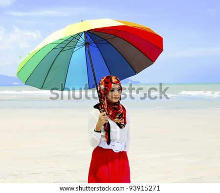 Portrait of pretty young Muslim woman at beach.