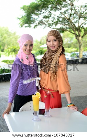 Portrait of pretty young Muslim woman smile when meet together at cafe