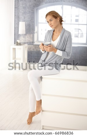 Portrait of pretty young woman at home, sitting in bright living room, daydreaming with tea mug in hands.?