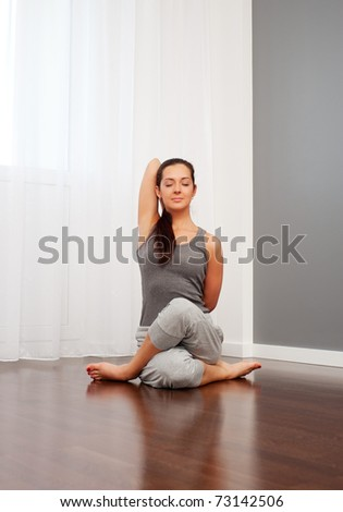 portrait of pretty young woman doing yoga exercise on floor
