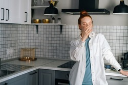Portrait of pretty young woman drinking white wine standing in light kitchen room. Dreamy lady tasting champagne alone while preparing food. Concept of leisure activity red-haired female at home