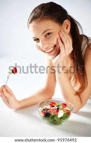 Portrait of pretty young woman eating vegetable salad